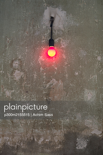 Germany, Berlin, Kreuzberg, Red light bulb on old wall - p300m2155515 by Achim Sass