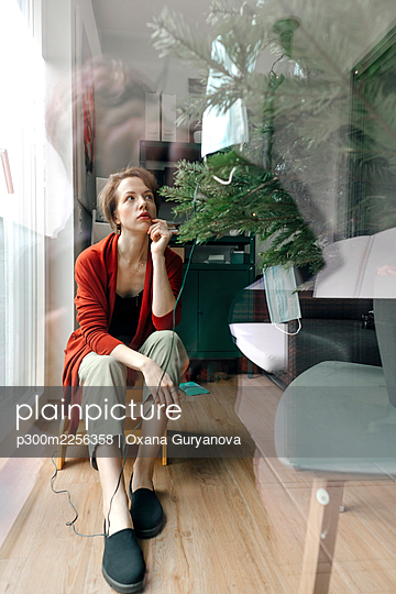 Woman sitting by Christmas tree seen through glass at home during pandemic - p300m2256358 by Oxana Guryanova