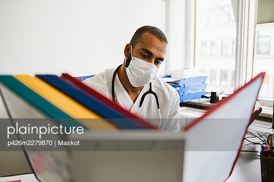 Male healthcare worker reading files at medical clinic during COVID-19 - p426m2279870 by Maskot