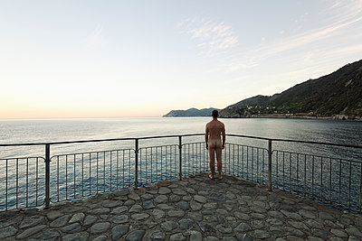 Naked man looks at the sea - p1383m1511310 by Wolfgang Steiner