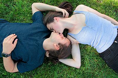 Junges Paar im Park küsst sich - p258m1444960 von Katarzyna Sonnewend