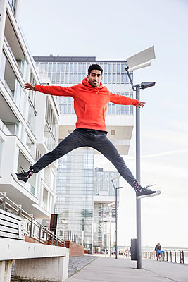 Germany, Cologne, portrait of young man jumping in the air - p300m2004382 von Jan Tepass