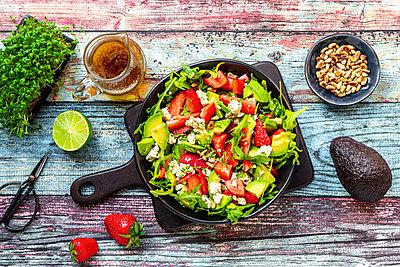 Strawberry avocado salad with feta, rocket, pine nuts and cress - p300m2103844 von Sandra Roesch