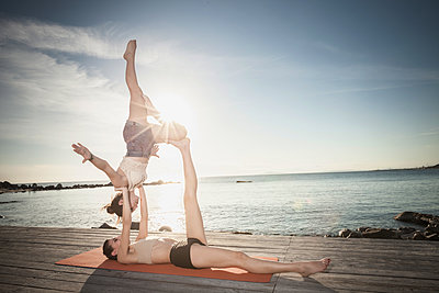 Women practising acro yoga at seaside - p429m2090967 by ROBERTO PERI