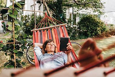 Frau mit E-Book entspannt in der Hängematte  - p586m1178384 von Kniel Synnatzschke