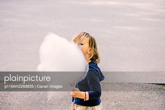 Cute young girl 3-4 years old eating cotton candy - p1166m2268835 by Cavan Images
