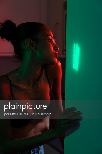 Portrait of beautiful young woman wearing bra and glasses in a dark illuminated room - p300m2012720 von Kike Arnaiz