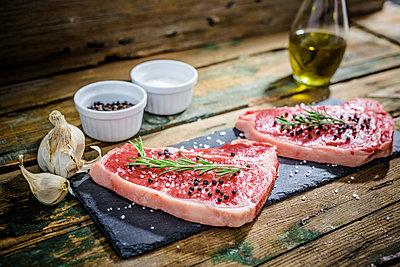 Raw beefsteak with rosemary, salt and pepper - p300m1535433 by Giorgio Fochesato