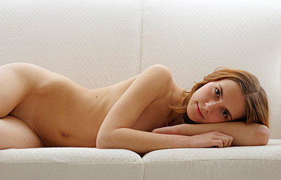 Woman lying naked on a couch - p5560156 by Wehner