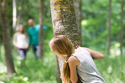 Girl hiking behind tree in woods - p62322000f by Eric Audras
