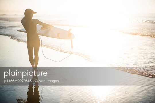 Independent Asian Woman looking out for sunrise summer surf at beach - p1166m2279618 by Cavan Images