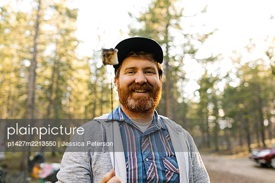 Portrait of smiling man holding roasted marshmallow on stick, Wasatch Cache National Forest - p1427m2213550 by Jessica Peterson