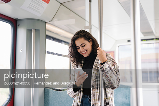 Smiling young woman using smartphone on a subway - p300m2143398 by Hernandez and Sorokina
