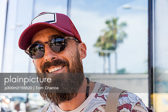 Smiling mature man with beard, red basecap and sunglasses - p300m2155820 by Tom Chance