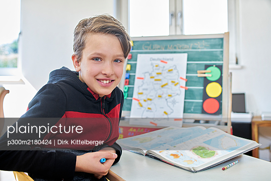 Portrait of smiling boy, learning at home - p300m2180424 by Dirk Kittelberger