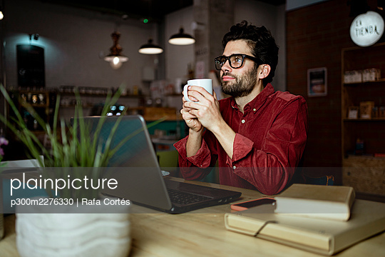Thoughtful male freelance worker with laptop having coffee in illuminated cafe - p300m2276330 by Rafa Cortés
