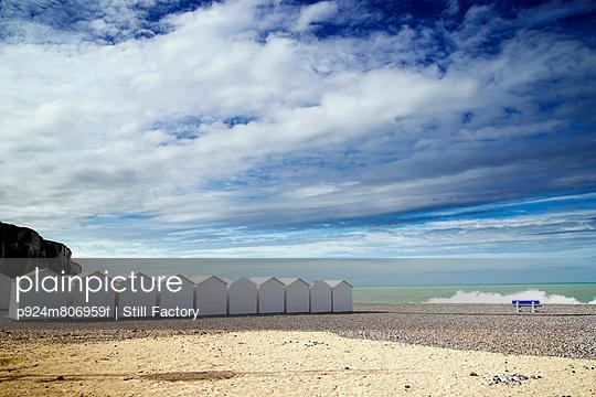 White beach huts in a row on shingle beach - p924m806959f by Still Factory