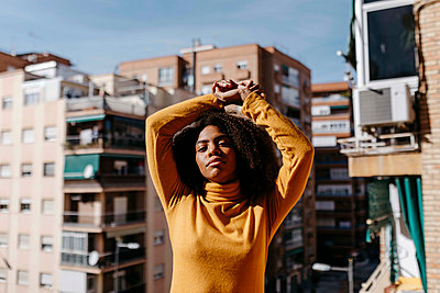 Woman stretching hand while standing at balcony - p300m2256661 by Tania Cervián