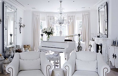 Grand piano and matching white armchairs with a collection of vases - p349m790418 by Brent Darby