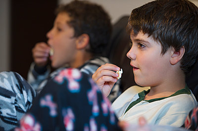 Hispanic boys eating popcorn and watching television - p555m1478251 by GM Visuals