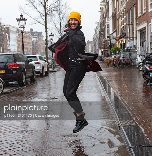 Young woman in coat jumping in puddle in rainy day on street. - p1166m2131170 by Cavan Images