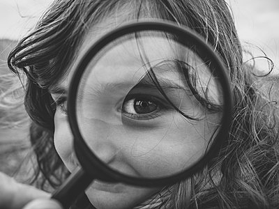Little girl looking through magnifying glass in black and white - p1522m2082752 by Almag