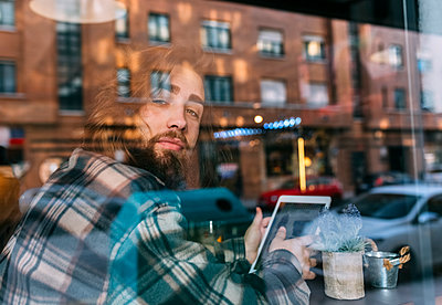 Portrait of stylish young man behind windowpane with tablet in a cafe - p300m1228749 by Marco Govel