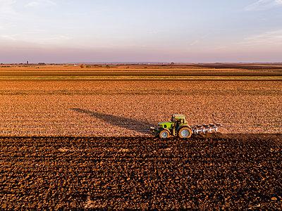 Serbia, Vojvodina. Tractor plowing field in the evening - p300m2069651 von oticki