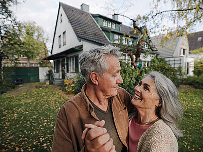 Happy senior couple in garden of their home in autumn - p300m2156106 by Gustafsson