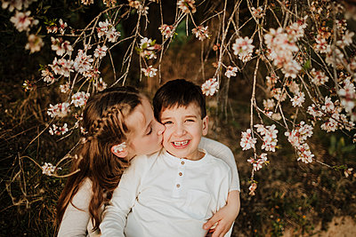 Sister kissing smiling brother while sitting under almond tree branches - p300m2265634 by Gala Martínez López