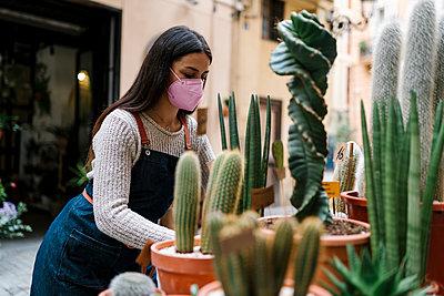 Valencia, Spain. Woman working in a florist's shop with a mask placing the plants and flowers in the shop. - p300m2274222 von Ezequiel Giménez