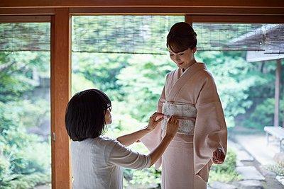 Young Japanese woman putting on traditional kimono - p307m2135281 by Yosuke Tanaka