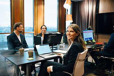 Portrait of female lawyer sitting with colleagues during meeting in office - p426m2270634 by Maskot