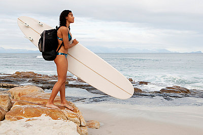 Woman carrying surfboard on beach - p42916162f by Clarissa Leahy
