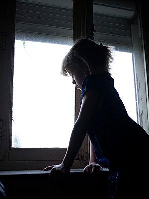 Mädchen blickt aus dem Fenster - p945m1467739 von aurelia frey