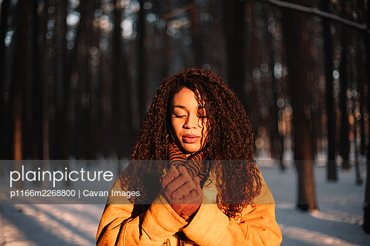 Portrait of beautiful young woman standing in park during cold winter - p1166m2268800 by Cavan Images