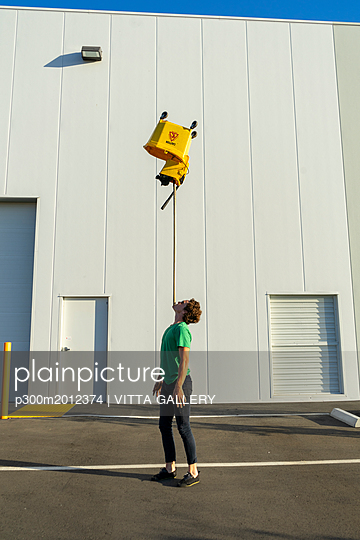Acrobat balancing bucket on mop on his chin - p300m2012374 von VITTA GALLERY