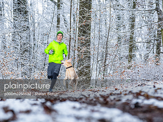Young male athlete jogging with Labrador retriever during winter in forest - p300m2256632 by Stefan Schurr