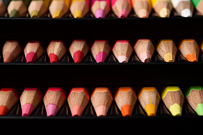 Watercolor pencils lined up in a black plastic box. - p1166m2095582 by Cavan Images