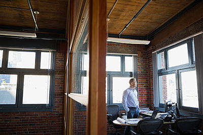 Pensive businessman looking out office window - p1192m1085814f by Hero Images