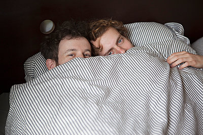 High angle portrait of young gay couple peeking through sheet in bed - p301m961100f by Halfdark