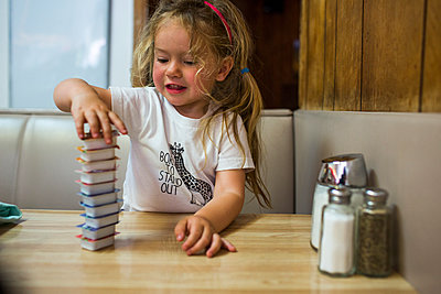 Smiling Caucasian girl stacking jelly containers in restaurant booth - p555m1521336 by Adam Hester