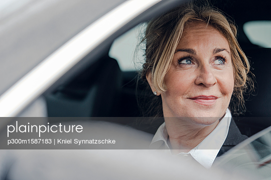 Portrait of smiling senior businesswoman in car - p300m1587183 von Kniel Synnatzschke