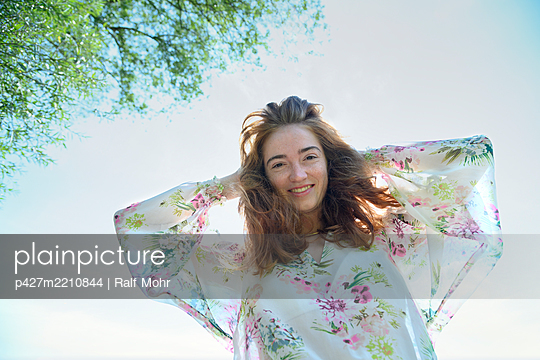 Happy woman in a flower dress - p427m2210844 by Ralf Mohr