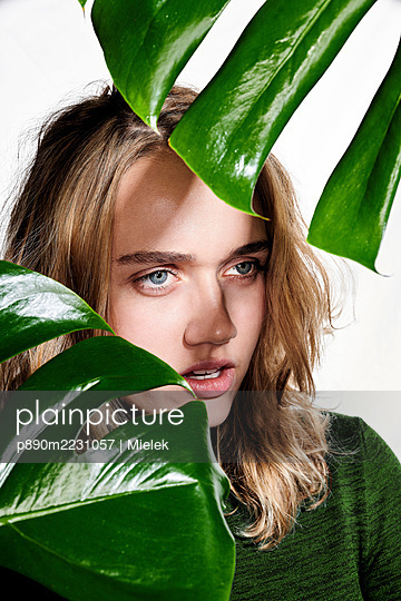 Young woman hiding behind foliage plant - p890m2231057 by Mielek