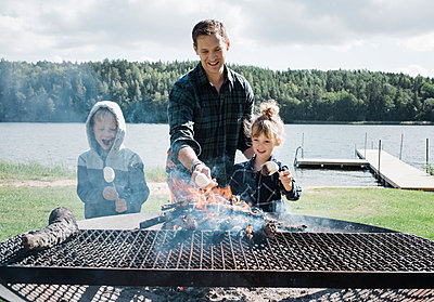 father toasting marshmallows with his kids at the beach on a BBQ - p1166m2212892 by Cavan Images