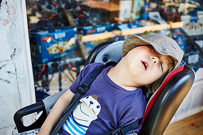 Toddler boy sleeping in child seat - p1511m2223049 by artwall