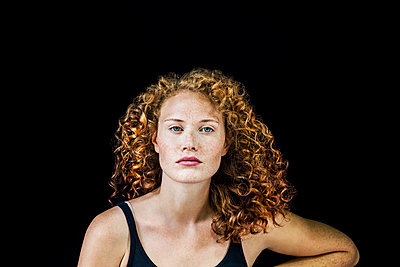 Portrait of freckled young woman with curly red hair in front of black background - p300m2029026 by Jo Kirchherr