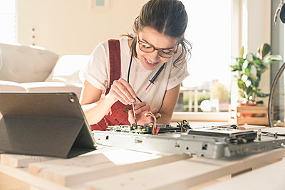 Young woman working on computer equipment at home next to tablet - p300m2104045 by Uwe Umstätter