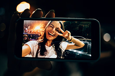 Young woman using smartphone in the city at night, taking a selfie - p300m2140965 by alev